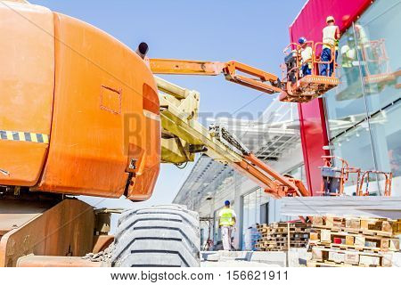 Cherry picker has elevated platform with riggers in safety basket at construction site.