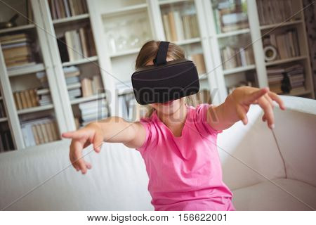 Happy girl looking through virtual reality headset in living room at home