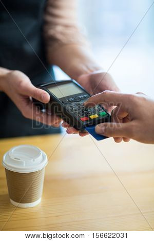 Man paying bill through payment terminal in cafe