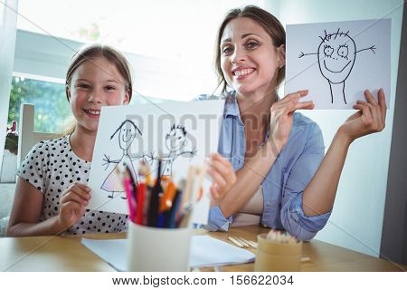 Mother and daughter showing their drawings at home