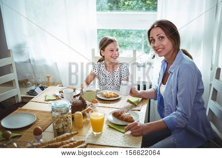 Mother and daughter having breakfast at home