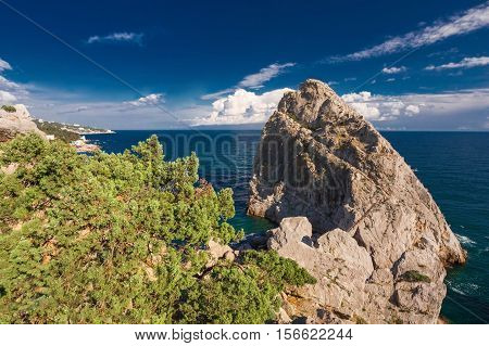 large rock standing in the sea and blue sky with white clouds
