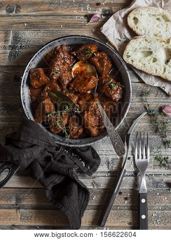 Beef stew in a frying pan on a wooden rustic table. Top view