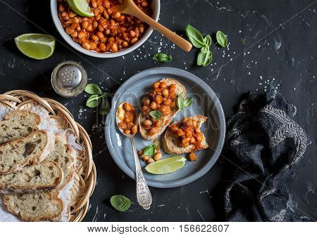 Bruschetta with beans in tomato sauce. Delicious vegetarian appetizer or snack. On a dark background top view