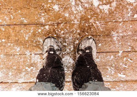 Top View Of Feet In Boots And Gaiters Snow Protection In The Snow On The Wooden Floor