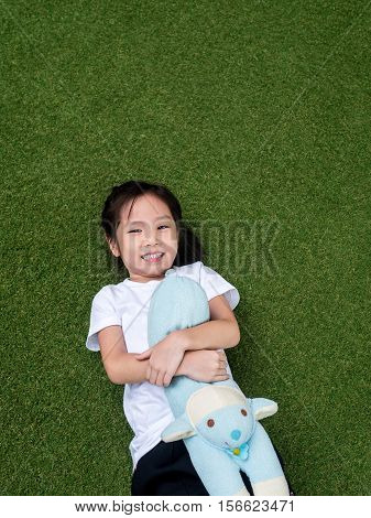 little asian kid girl lay down on the lawn with her doll