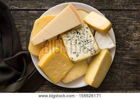 Different kinds of cheeses on old wooden table. Top view.