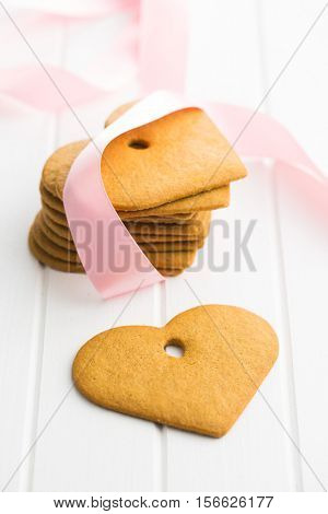 Tasty gingerbread hearts on white table.