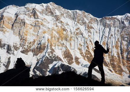 Silhouette backpacker on the rock and Annapurna I Background (8,091m) from Annapurna Basecamp ,Nepal.