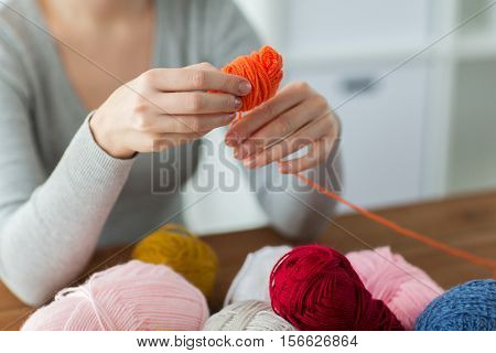 knitting, people and needlework concept - woman pulling yarn up into ball