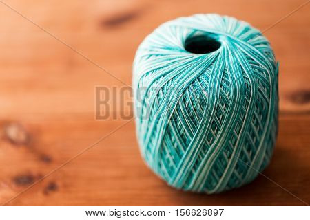 handicraft , knitting and needlework concept - ball of turquoise cotton yarn on wood