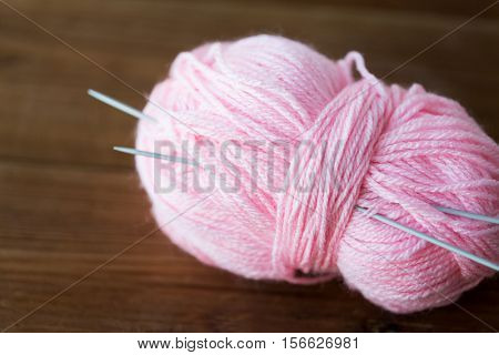 handicraft and needlework concept - knitting needles and ball of pink yarn on wood