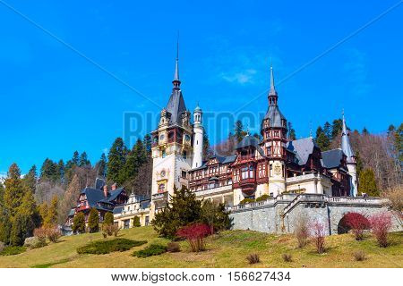 Spring view of Peles Castle with snowy mountains in the background, Sinaia, Romania