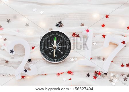Christmas and New Year 2017 background. Travel symbol - compass and confetti on white fabric.