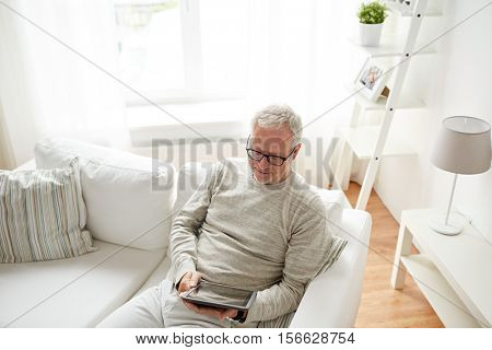 technology, people and lifestyle concept - senior man with tablet pc computer at home