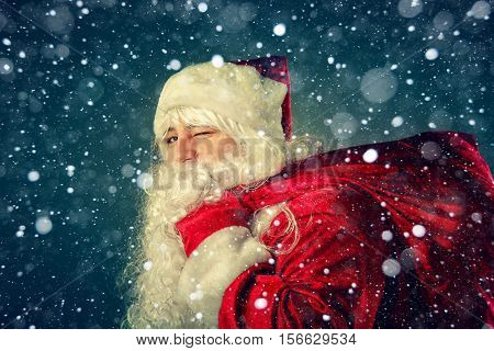 Portrait of Santa Claus. Santa Claus carries a bag with gifts. Christmas Fantasy.