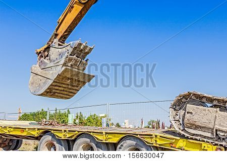 Heavy excavator it climbs on low platform trailer over back ramp carrying two buckets inserted into one another.