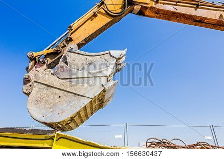 Excavator buckets are vertically arranged various types sorted by size transported.