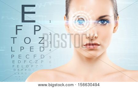 Beautiful woman with laser hologram and test vision table over cyan background.