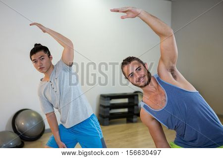 Smiling two men doing aerobic exercise in fitness studio