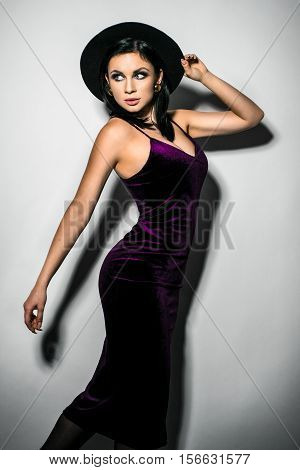 Beautiful young woman in a black hat and a purpule dress