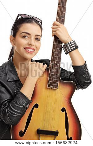 Young woman in a leather jacket holding an acoustic guitar isolated on white background