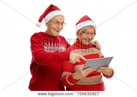 Seniors with Santa hats looking at a tablet isolated on white background