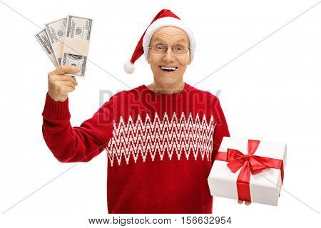Happy senior holding a Christmas present and bundles of money isolated on white background