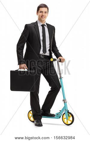 Full length portrait of a young businessman with a briefcase and a scooter isolated on white background