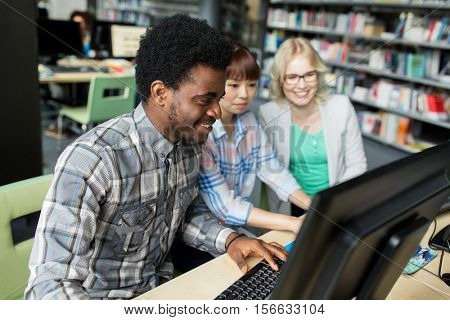 people, education, technology and school concept - group of happy smiling international students with computers at library in university