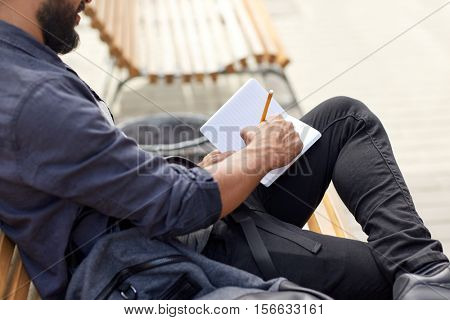 lifestyle, freelance, inspiration and people concept - close up of man with bag writing to notebook or diary sitting on city street bench