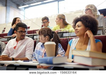 education, high school, university, learning and people concept - group of international students with books and coffee at lecture hall