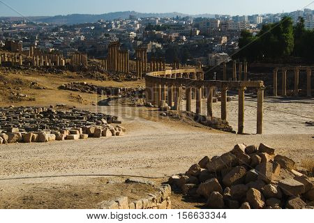 Photo of the View ruins Oval Forum and long colonnaded street or cardo ancient Greco-Roman city Gerasa. Modern Jerash on background. Tourism industry, tourist attraction, travel concept.