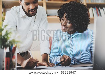 Two young coworkers working together in a modern office.Black business people discussing new startup project.Horizontal, blurred