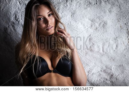 Fashion portrait of beautiful female model posing in black lingerie near white wall