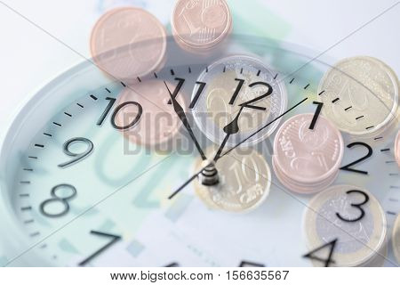 time, business, money making and finance concept - clock over euro coins and banknotes with double exposure effect