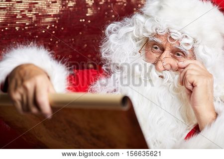 Portrait of happy Santa Claus holding Christmas letter .