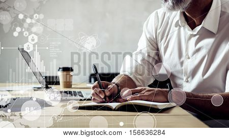 Concept of digital screen with global virtual icon, diagram, graph interfaces.Adult successful businessman wearing a classic glasses and working on laptop at the wood table in modern loft.Wide