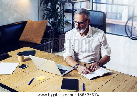 Adult successful businessman wearing a classic glasses and working at the wood table in modern coworking office.Stylish bearded middle age man making notes notebook. Horizontal, blurred background