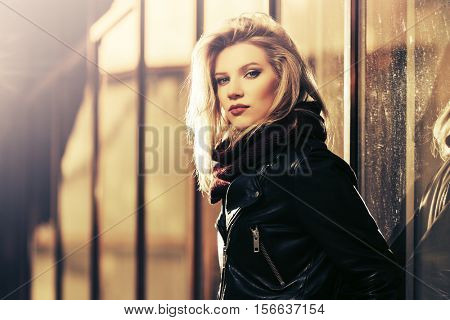 Young blond woman in leather jacket at the mall window. Stylish fashion model outdoor