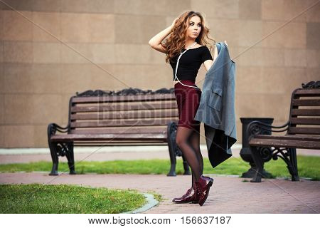 Young woman with a coat walking on city street. Stylish fashion model with long curly hairs outdoor