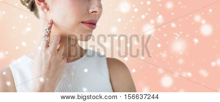beauty, christmas, holidays, people and luxury concept - close up of beautiful woman with golden ring and diamond earring over beige background and snow