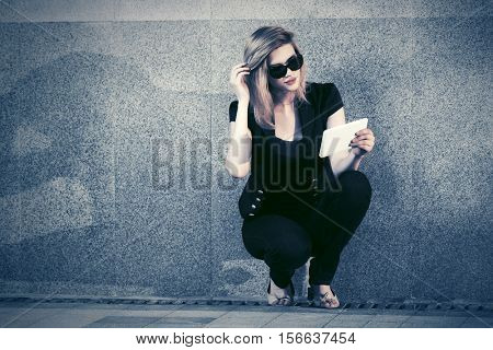 Young woman with tablet computer sitting at the wall. Stylish fashion model in sunglasses outdoor