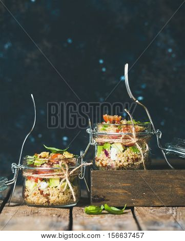 Healthy homemade jar quinoa salad with cherry tomatoes, sun-dried tomatoes, avocado and basil. Detox, dieting, vegetarian, vegan, clean eating food concept. Dark blue background, copy space