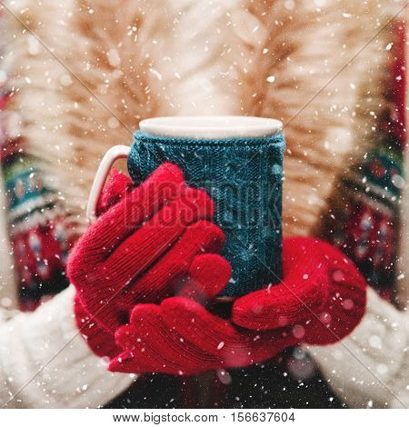Female hands holding knitted winter mug close up. Woman hands in red mittens holding a cozy knitted cup with hot cocoa, tea or coffee. Winter and Christmas time concept.