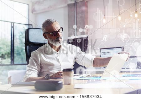 Concept of digital screen with virtual icon, diagram, graph and interfaces.Adult professional stock trader wearing a classic glasses working at the wood table in modern coworking studio.Horizontal