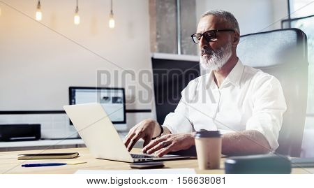 Middle age financial analyst wearing a classic glasses and working at the wood table with exchange markets.Stylish bearded businessman using laptop on workplace. Horizontal, blurred