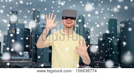 technology, augmented reality, winter, christmas and people concept - happy young man with virtual headset or 3d glasses playing game over singapore city skyscrapers background and snow