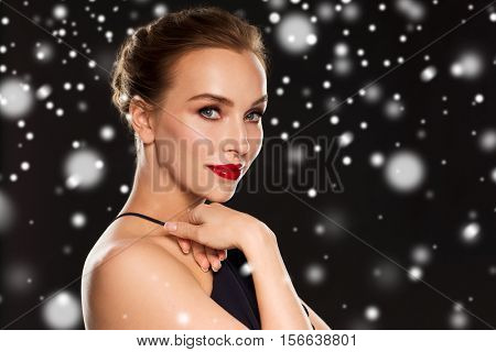 people, christmas, holidays, luxury and fashion concept - beautiful woman with red lips over black background and snow