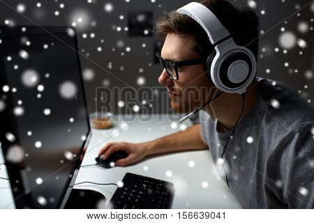 technology, gaming, entertainment, let's play and people concept - young man in headset and glasses with pc computer playing game at home and streaming playthrough or walkthrough video over snow